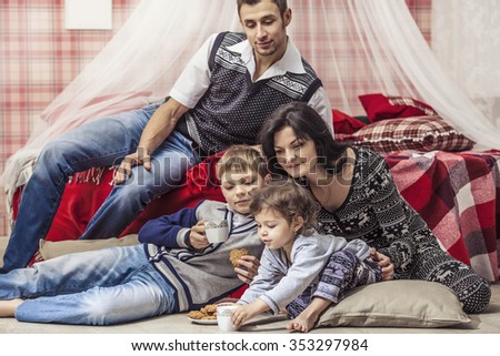 Family mother father children in the bedroom at home drinking tea with biscuits in the red Christmas interior - stock photo