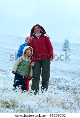 Family (mother with children) walk and play on autumn  mountain plateau with first winter snow - stock photo