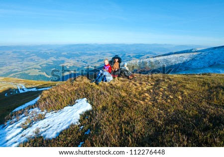 Family (mother with children) walk on autumn  mountain plateau first winter snow - stock photo