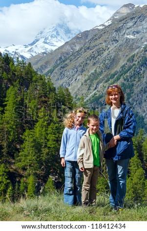 Family (mother with children) walk on summer Alps mountain (Switzerland, Zermatt, Matterhorn mount view) - stock photo