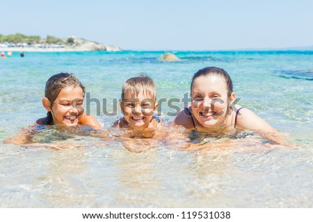 Family - mother with her kids have fun and swimming in the transparent sea - stock photo