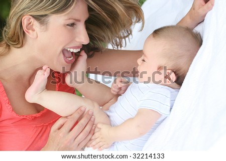 Family: mother with infant baby boy son, smiling and happy - stock photo