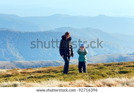 Family (mother with son) walk and make photo on autumn mountain plateau. - stock photo