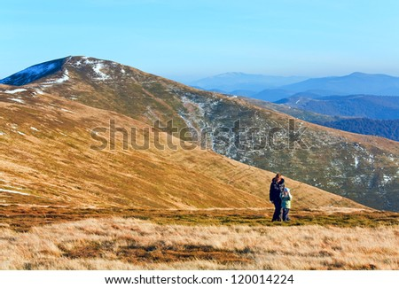 Family (mother with son) walk and make photo on autumn  mountain plateau first winter snow - stock photo