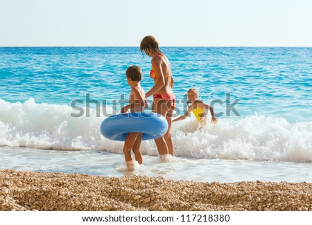 Family (mother with two children) have the water-based recreation on white Egremni beach (Ionian sea, Lefkada, Greece) - stock photo