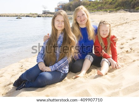 Family - mother with two daughters of different age, sxiteen and nine, sit on beach, recorded in Saint Constantine and Helen resort, Bulgaria. - stock photo