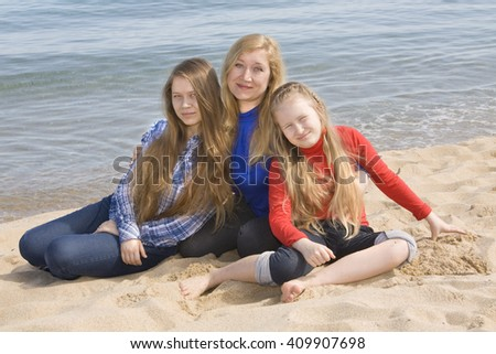 Family mother with two daughters  of sixteen and nine years on beach, European, sit on sea beach. - stock photo