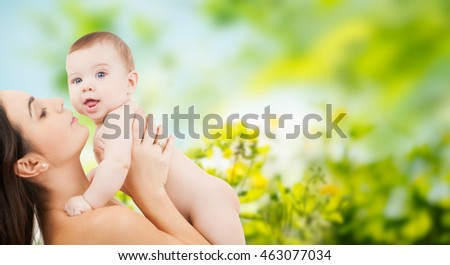family, motherhood, parenting, people and child care concept - happy mother holding adorable baby over green natural background