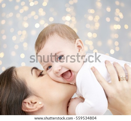 family, motherhood, parenting, people and child care concept - happy mother kissing adorable baby over holidays lights background