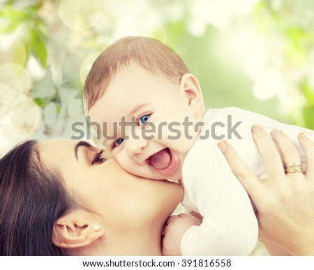 family, motherhood, spring, summer and people concept - happy laughing baby playing with mother over green blooming garden background