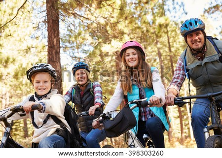 Family mountain biking in a forest, looking to camera - stock photo