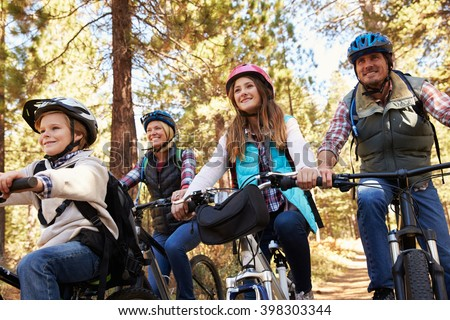 Family mountain biking in a forest, low angle front view - stock photo