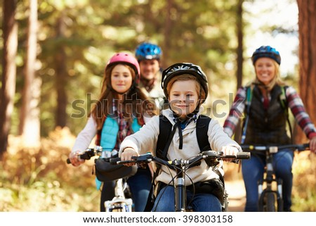 Family mountain biking on forest trail, front view, close-up - stock photo