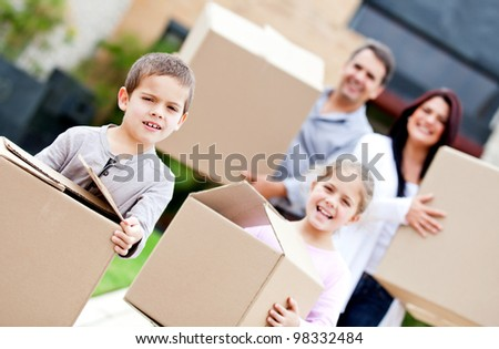 Family moving home and carrying cardboard boxes - stock photo