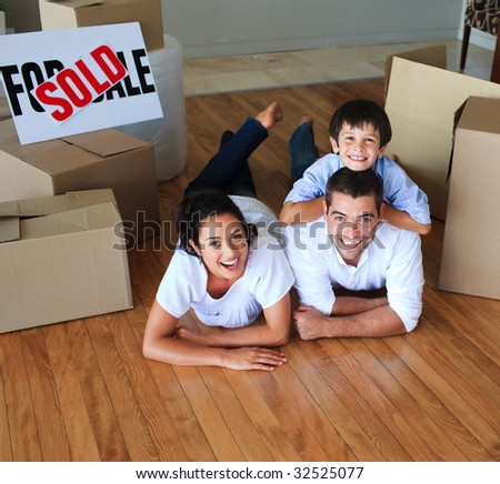 Family moving house lying on floor smiling at the camera