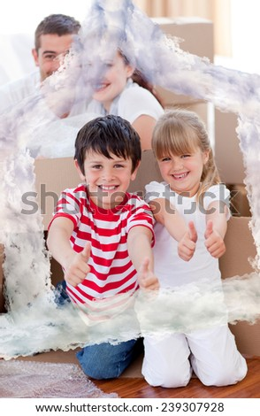 Family moving house with boxes and thumbs up against house outline in clouds - stock photo