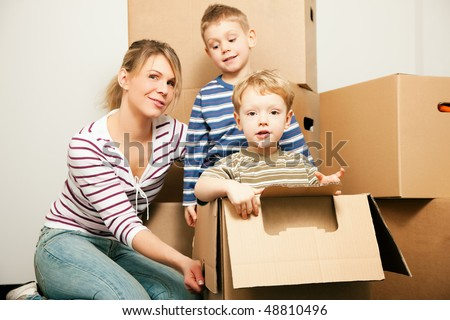 Family moving in their new house. The sons are sitting inside the moving boxes, everybody is looking rather cheerful - stock photo