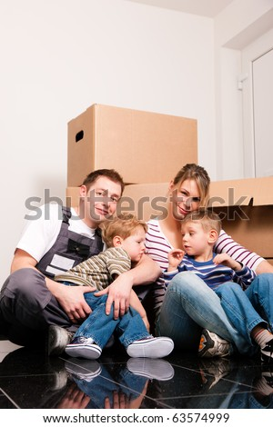 Family moving in their new house. They are sitting in front of a stack of moving boxes being happy. Father is dressed in a way that can also represent a mover - stock photo