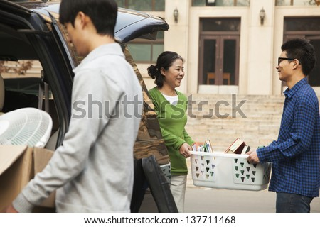 Family moving their son into dormitory on college campus - stock photo