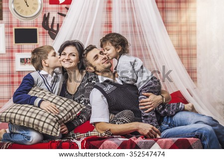 Family mum dad and kids together at home in the cosy atmosphere of the bedrooms in winter interior - stock photo