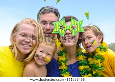 Family of Brazilian soccer fans commemorating victory. - stock photo