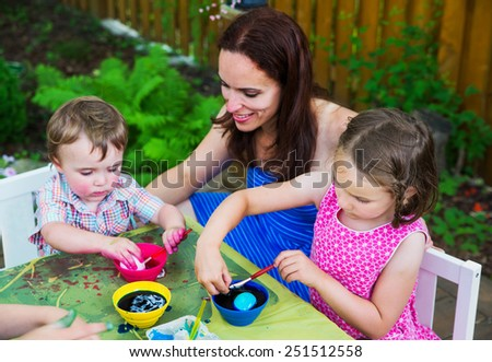Family of children painting and decorating eggs outside during Easter in the spring season in a garden setting. . Mother smiles at her boy as he color dyes an egg pink.   Part of a series.    - stock photo