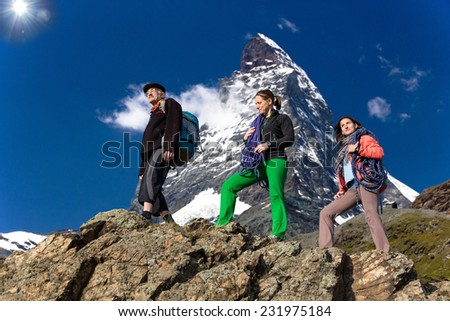 Family of climbers. Farther and daughters walk on the mountain ridge. High alpine landscape on the background - stock photo