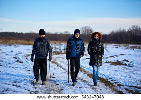 Family of farmers having a walk through the countryside in a sunny winter day
