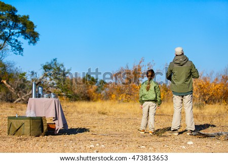 Family of father and child on African safari vacation enjoying bush breakfast