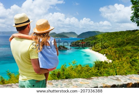 Family of father and daughter enjoying aerial view of picturesque Trunk bay on St John island, US Virgin Islands considered by many as most beautiful beach in Caribbean - stock photo
