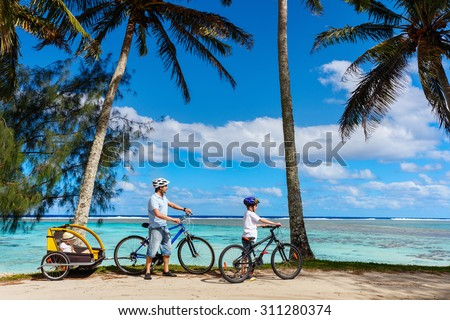 Family of father and kids biking at tropical beach - stock photo