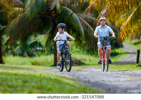 Family of father and son biking at tropical settings