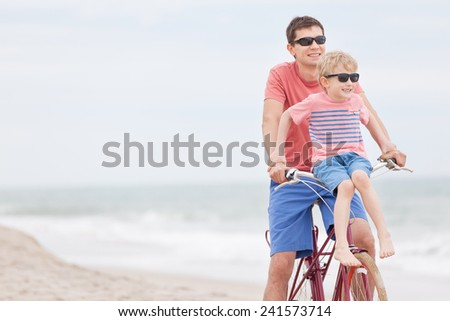 family of father and son enjoying riding bicycle together at the beach - stock photo