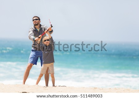 family of father and son playing with kite at the beach being active and happy enjoying vacation together, vacation and lifestyle concept