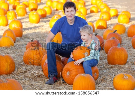 family of father and son spending fun time together at the pumpkin patch