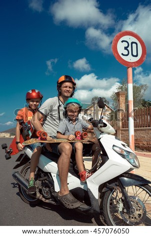 Family of father and two kids on motorbike. - stock photo