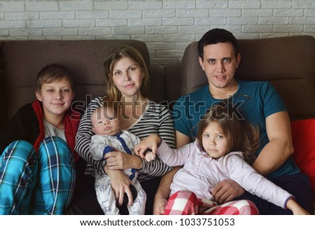 family of father, mother and three children at home