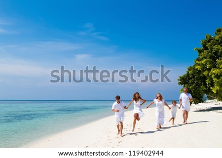 Family of five celebrating a wedding anniversary running on a beautiful tropical beach - stock photo