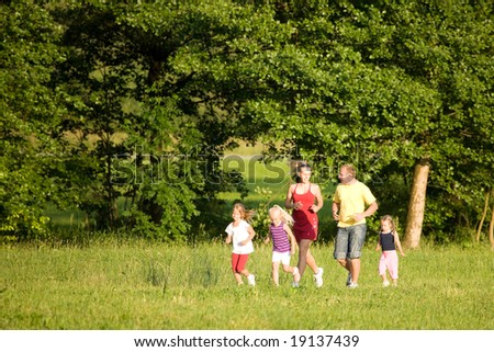 Family of five exercising outdoors, jogging thru the woods - stock photo