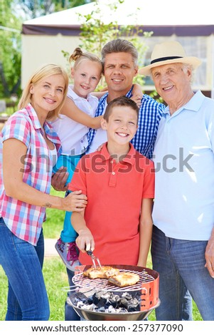 Family of five having barbecue outdoor - stock photo