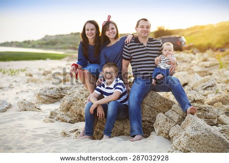 Family of five having fun on the beach. Summer vacation and car travel concept