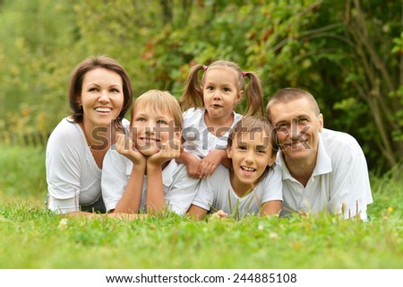 Family of five lying on grass in summer park - stock photo