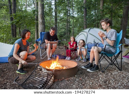 family of five people camping and having fun cooking over fire - stock photo