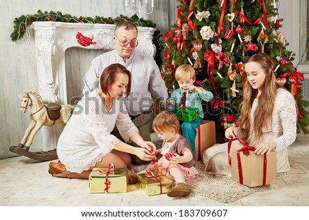 Family of five sits near Christmas tree untying ribbons on gift boxes
