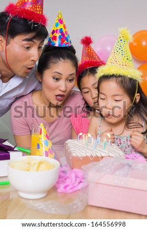 Family of four blowing cake at a birthday party - stock photo