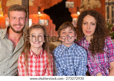 family of four closeup portrait on background of wall with pelts and photos - stock photo