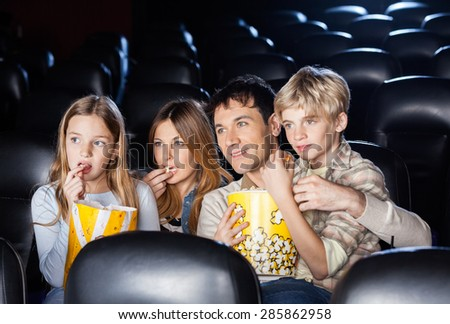 Family of four eating popcorn while watching film in movie theater - stock photo
