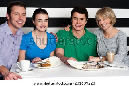 Family of four enjoying breakfast together - stock photo