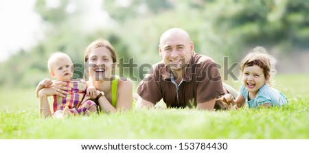 family of four enjoying time at green grass in summer p