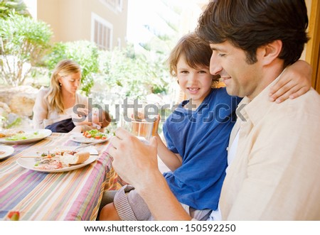 Family of four gathering around a table with food in a home porch garden outdoors with mother, father, baby girl, and a young boy drinking water with dad. - stock photo